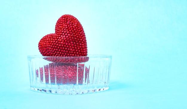 Giorno di san valentino. cuori lucidi rossi sul cuore di vetro. san valentino. pendente a cuore.