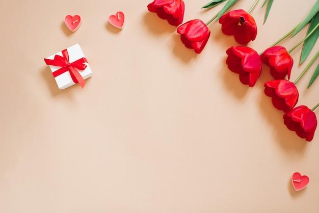 Sfondo romantico di san valentino. tulipani rossi, un regalo con un fiocco e cuori di candela su uno sfondo beige con spazio di copia. lay piatto