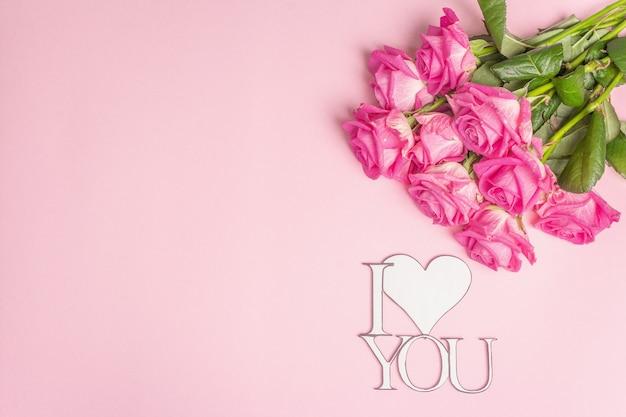 Superficie di san valentino con rose fresche, cuore e lettere ti amo