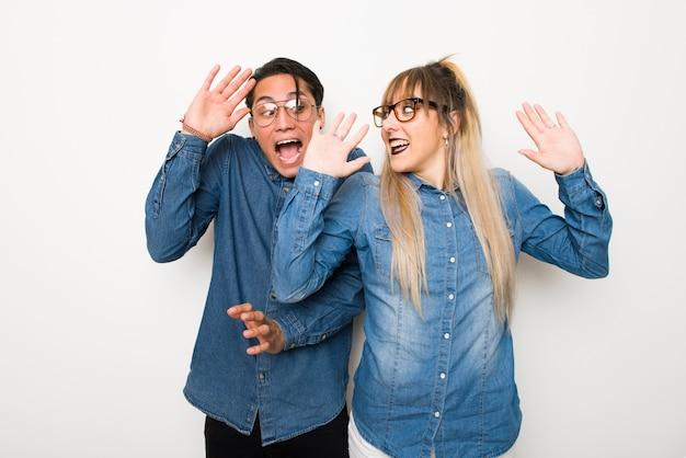 Nel giorno di san valentino coppia giovane con gli occhiali con espressione facciale sorpresa e scioccata