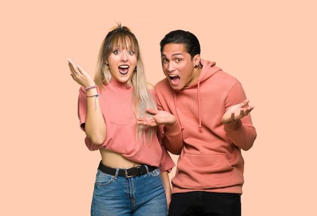Nel giorno di san valentino coppia giovane con sorpresa e scioccato espressione facciale su sfondo rosa