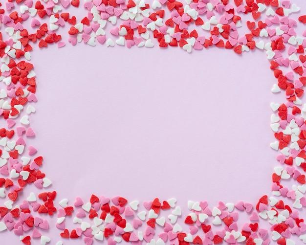 Cornice di san valentino composta da cuoricini di zucchero rosso, bianco e rosa