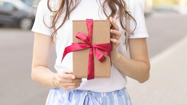 Regalo di san valentino. mani della donna di bellezza che tengono il contenitore di regalo con l'arco rosso sopra il fondo di festa con il bokeh d'ardore dei cuori, primo piano. colori pastello. fondale in formato grandangolare