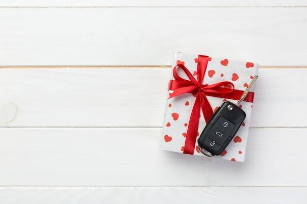 Confezione regalo di san valentino con nastro rosso e auto chiave. lay piatto
