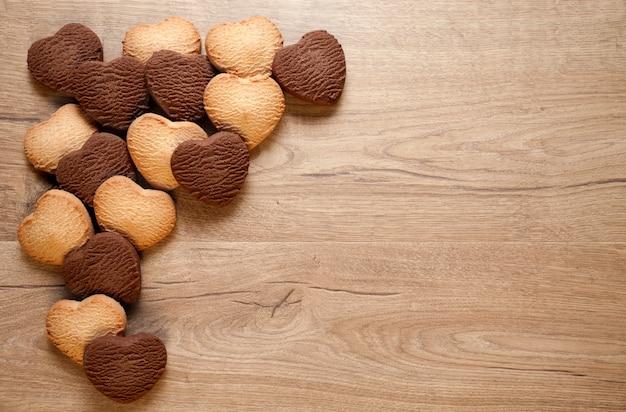 Biscotti del cuore di san valentino su fondo in legno. biscotti al burro e cioccolato al forno e posto per il testo.