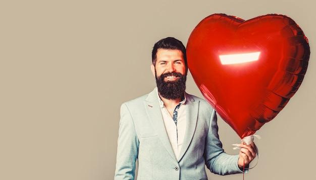 Valentino uomo con mongolfiera rossa. uomo felice con mongolfiere a forma di cuore. san valentino. cuore rosso. cuori d'amore.