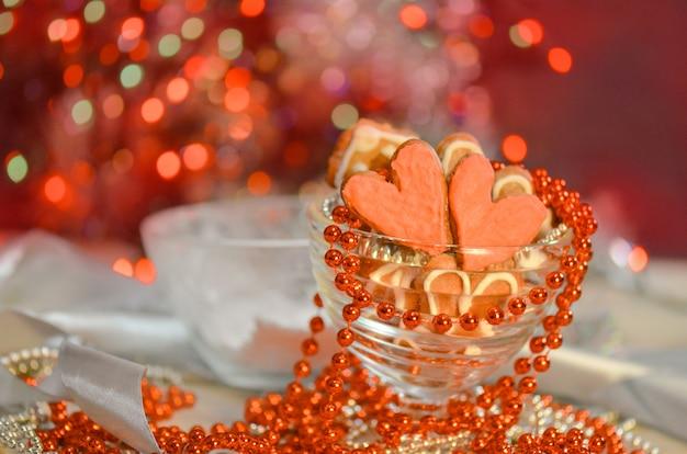 Biscotti cuore rosa di san valentino sul tavolo di legno. biscotti a forma di cuore per san valentino. concetto di amore