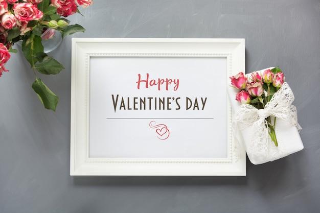 Carta di san valentino. mazzo delle rose e della cornice bianca con il regalo su gray.