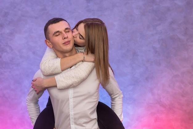 Il concetto di san valentino. fidanzato che tiene la sua bella coppia sulla schiena. emozioni da incontri