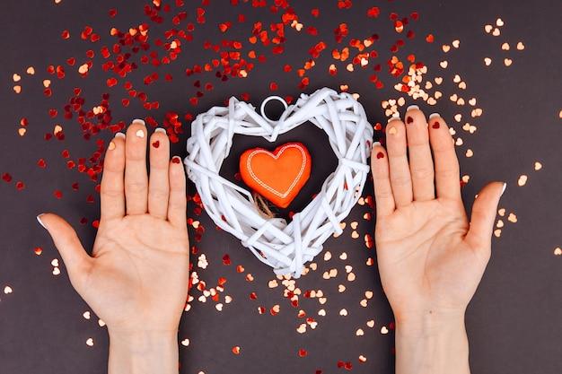 San valentino . il 14 febbraio. mani femminili, palme in su. vista dall'alto. copia spazio