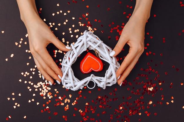 San valentino . il 14 febbraio. nelle mani della ragazza ci sono due cuori rosso e bianco. ci sono molti piccoli cuori in un cerchio.