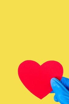 Concetto di san valentino 2021. la mano in guanti blu medici tiene una forma di cuore rosso