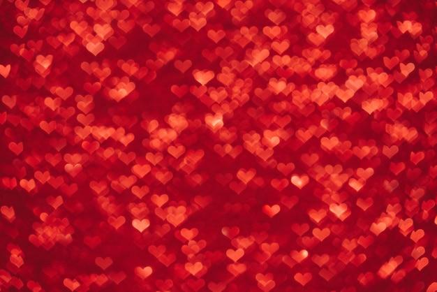 Sfondo di san valentino. bokeh illuminato rosso a forma di cuori. fondo rosso astratto con la luce vaga del bokeh del cuore.