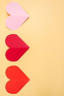 Sfondo di san valentino. cuori rosa e rossi su sfondo giallo pastello. concetto di san valentino. appartamento laico, vista dall'alto, copia dello spazio