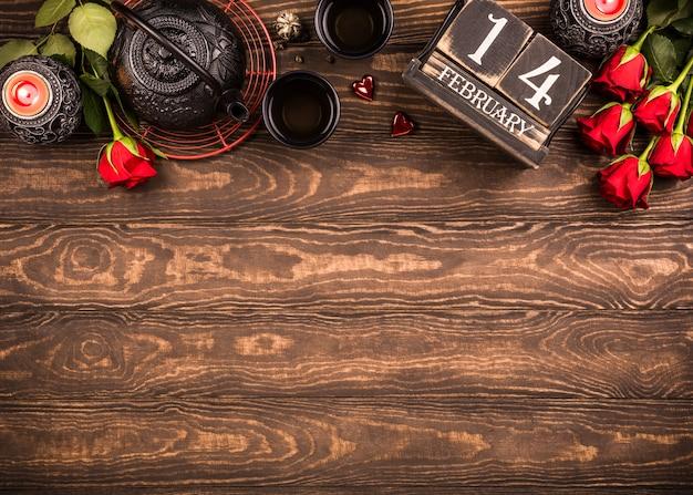 Fondo di san valentino con tè verde, teiera nera, candele, rose e calendario in legno