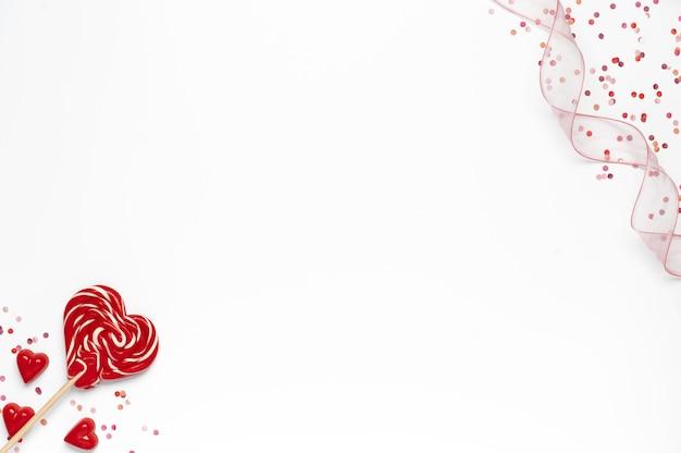 Sfondo di san valentino con lecca-lecca cuore, coriandoli e nastro su priorità bassa bianca
