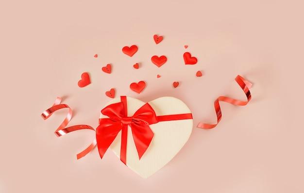 Sfondo di san valentino con forme di cuore confezione regalo a forma di cuore con un fiocco rosso su sfondo rosa. concetto di amore.