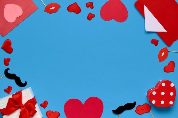 Sfondo di san valentino con busta rossa, regalo di san valentino, decorazioni di labbra, spazio di copia. vista dall'alto, piatto
