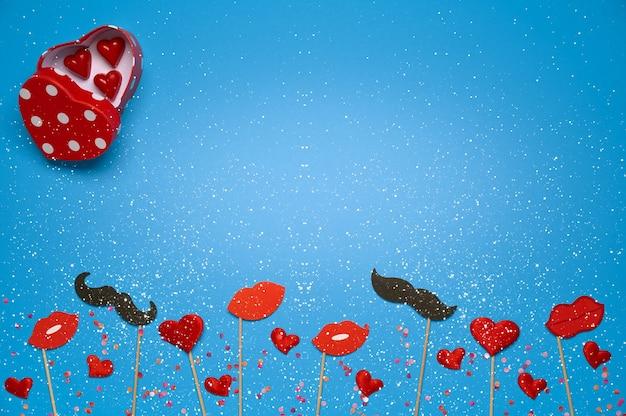 Modello di banner di san valentino con scatola di caramelle a forma di cuore, labbra rosse, regalo, decorazioni su sfondo blu con spazio di copia e fiocchi di neve. vista dall'alto, piatto