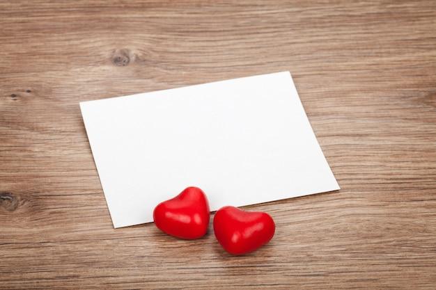 Cartolina d'auguri in bianco di san valentino e cuori di caramelle sul tavolo di legno