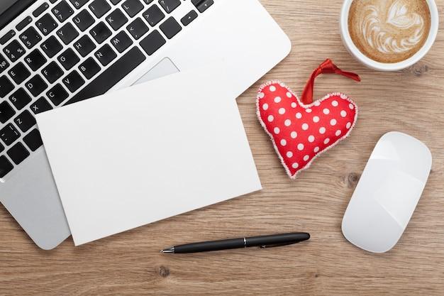 Biglietto di auguri vuoto di san valentino e cuore giocattolo sul posto di lavoro in ufficio