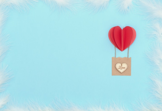 Sfondo blu di san valentino con palloncino cuore rosso con cesto con cuore in legno su di esso e piume bianche