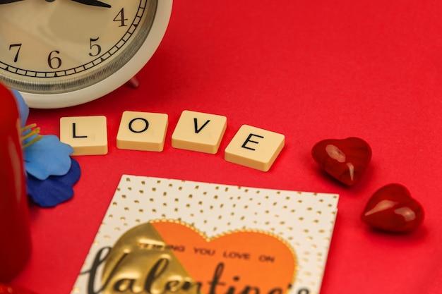 Celebrazione di san valentino, cuori rossi, parola amore e decorazione, concetto romantico, sfondo rosso foto ravvicinata