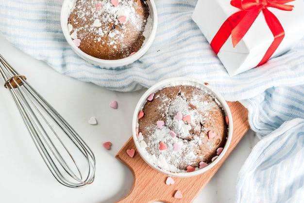 La torta o il brownie della tazza del cioccolato di san valentino con zucchero a velo e la caramella a forma di spruzza, tavola bianca, vista superiore
