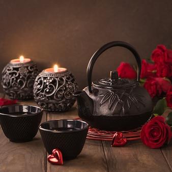 Composizione di san valentino con tè verde, teiera nera, candele e rose sulla tavola di legno. concetto di biglietto di auguri di san valentino con spazio di copia
