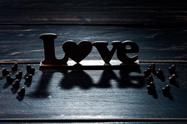 Composizione di san valentino con cuori e silhouette della parola amore sulla tavola di legno