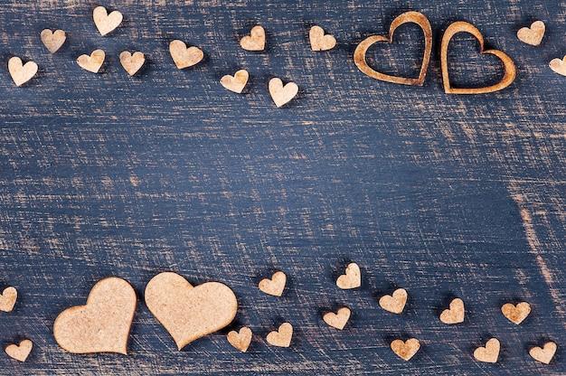 Composizione di san valentino con cuori rustici su tavola di legno. copia spazio