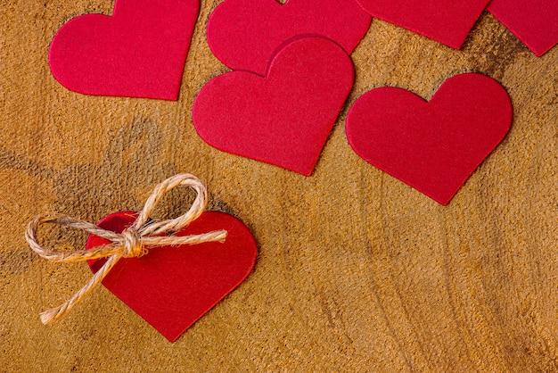 Composizione di san valentino con fondo in legno e cuori rossi