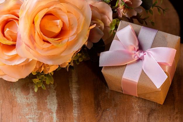 Composizione di san valentino su fondo in legno con regalo e fiori