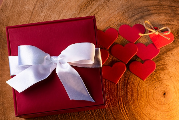 Composizione di san valentino su fondo in legno con regalo e cuori rossi