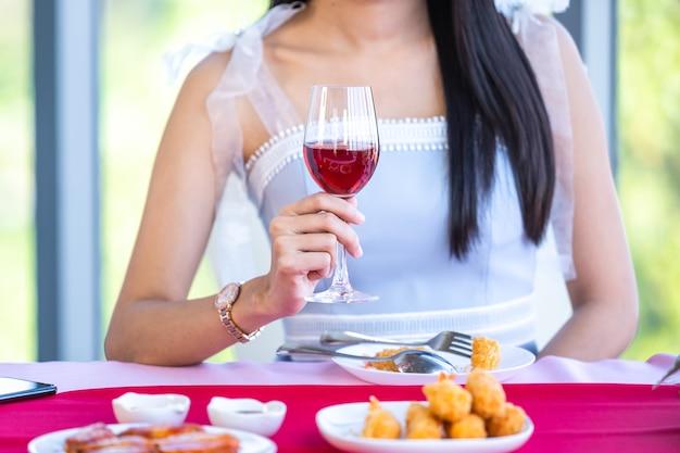 Concetto di san valentino, ragazza asiatica seduta a un tavolo cibo con bicchieri di vino e bouquet di rose rosse e rosa vino e aspettando il suo uomo sullo sfondo del ristorante