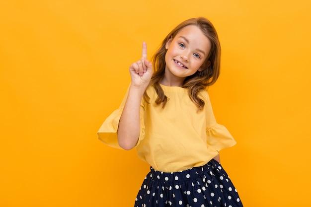 Concetto di san valentino. attraente ragazza affascinante bambino in una maglietta e gonna si presenta al muro su giallo con spazio di copia