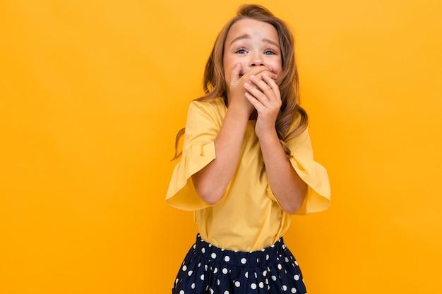 Concetto di san valentino. attraente ragazza affascinante bambino in una maglietta e gonna a sorpresa copre la bocca con la mano sul giallo con spazio di copia