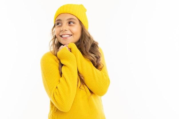Concetto di san valentino. ragazza adolescente carina in accoglienti abiti gialli su sfondo bianco