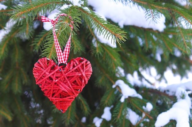 Concetto di san valentino. cuore rosso in legno decorativo su un ramo di abete innevato