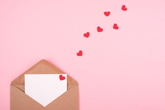 Concetto di san valentino. busta con una lettera d'amore su uno sfondo rosa.