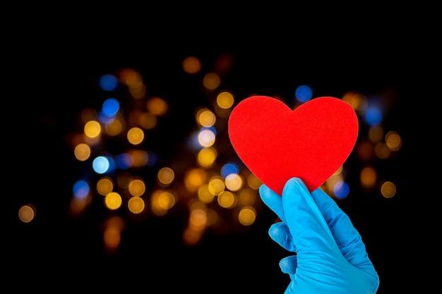 Concetto di san valentino. una mano in guanti blu medici tiene una forma di cuore rosso