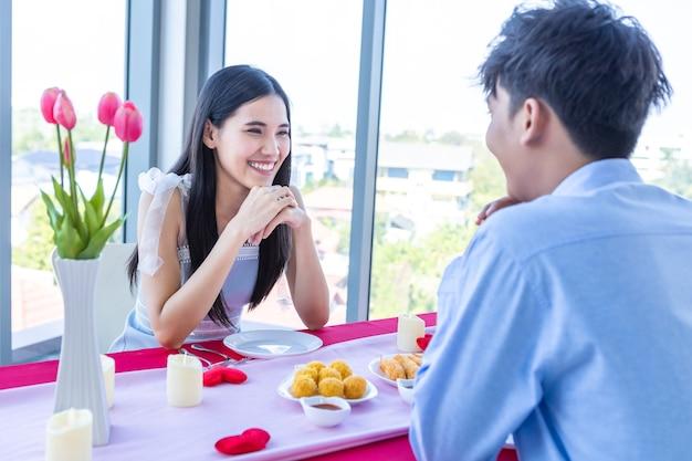 Concetto di san valentino, felice coppia asiatica giovane dolce che ha romantico il pranzo con un mazzo di rose sullo sfondo del ristorante.