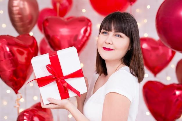 Concetto di san valentino - donna sognante felice con scatola regalo su sfondo di palloncini a forma di cuore rosso
