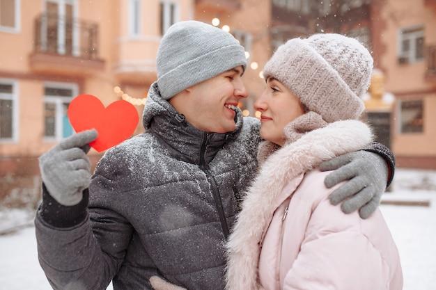 Concetto di san valentino, coppia di innamorati bacio e abbraccio in un parco innevato di inverno. il giovane tiene un cuore di carta rosso mentre celebra la giornata degli innamorati con la sua ragazza. una coppia che si sente calda insieme.