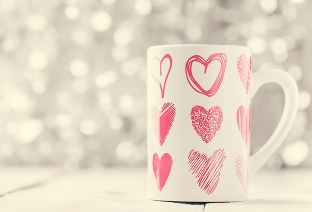 Concetto di san valentino con tazza con stampa a forma di cuore su bokeh bianco