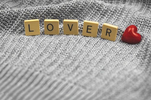 Concetto di san valentino con amante della parola, cuore rosso su una foto di sfondo di un maglione lavorato a maglia