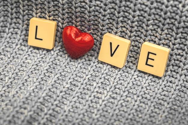 Concetto di san valentino, parola amore fatta con cubi e cuore di vetro rosso, sfondo a maglia, foto di cartolina d'auguri