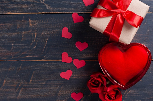San valentino. decorazione con scatola regalo, cuori rossi e fiori su fondo di legno rustico