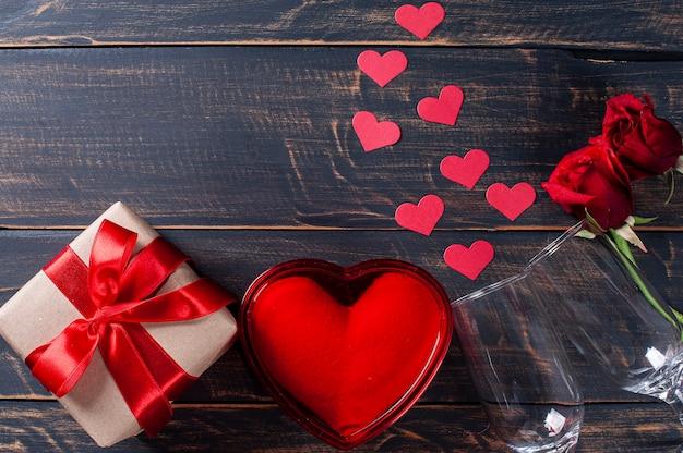 San valentino. decorazione con scatola regalo, cuori rossi su fondo di legno rustico