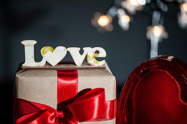 San valentino. decorazione con la parola amore e confezione regalo e cuori rossi